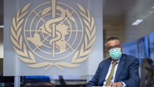 Usando máscara, o diretor-geral Tedros Adhanom posa em frente ao símbolo da Organização Mundial da Saúde