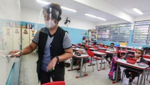 funcionário em escola com face shield e alguns alunos sentados nas mesas