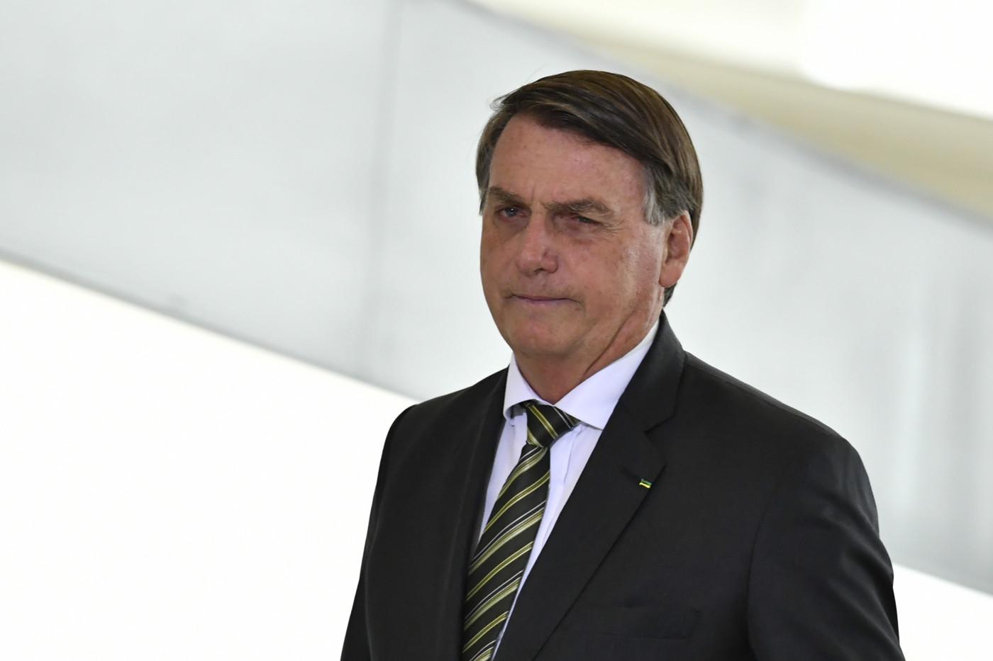 homem de terno e gravata diante de fundo branco olhando para o horizonte
