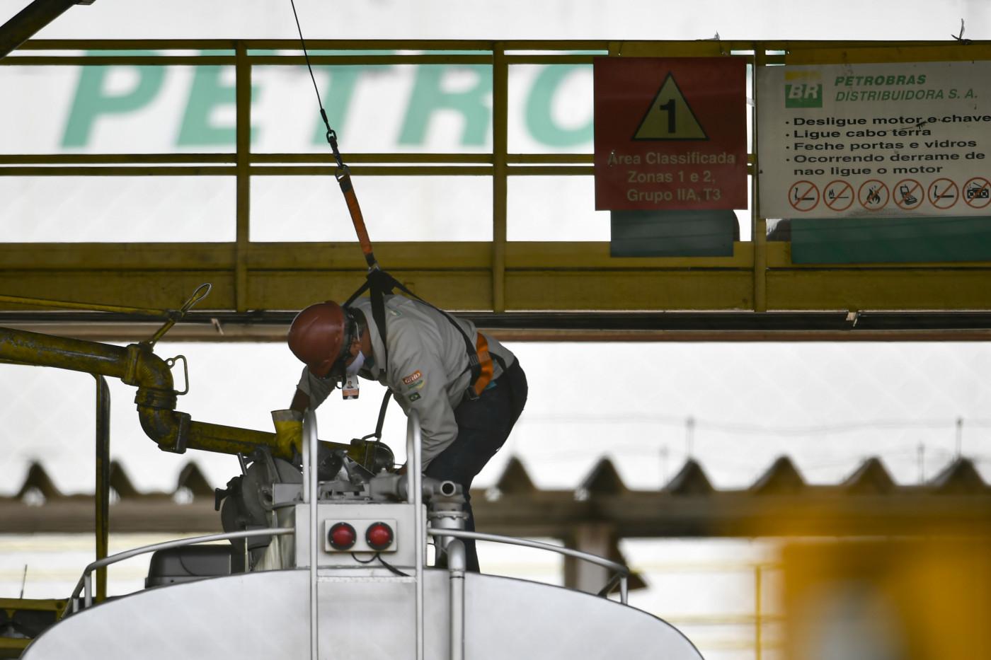Homem trabalhando próximo a um tanque da estatal brasileira de petróleo, a Petrobrás