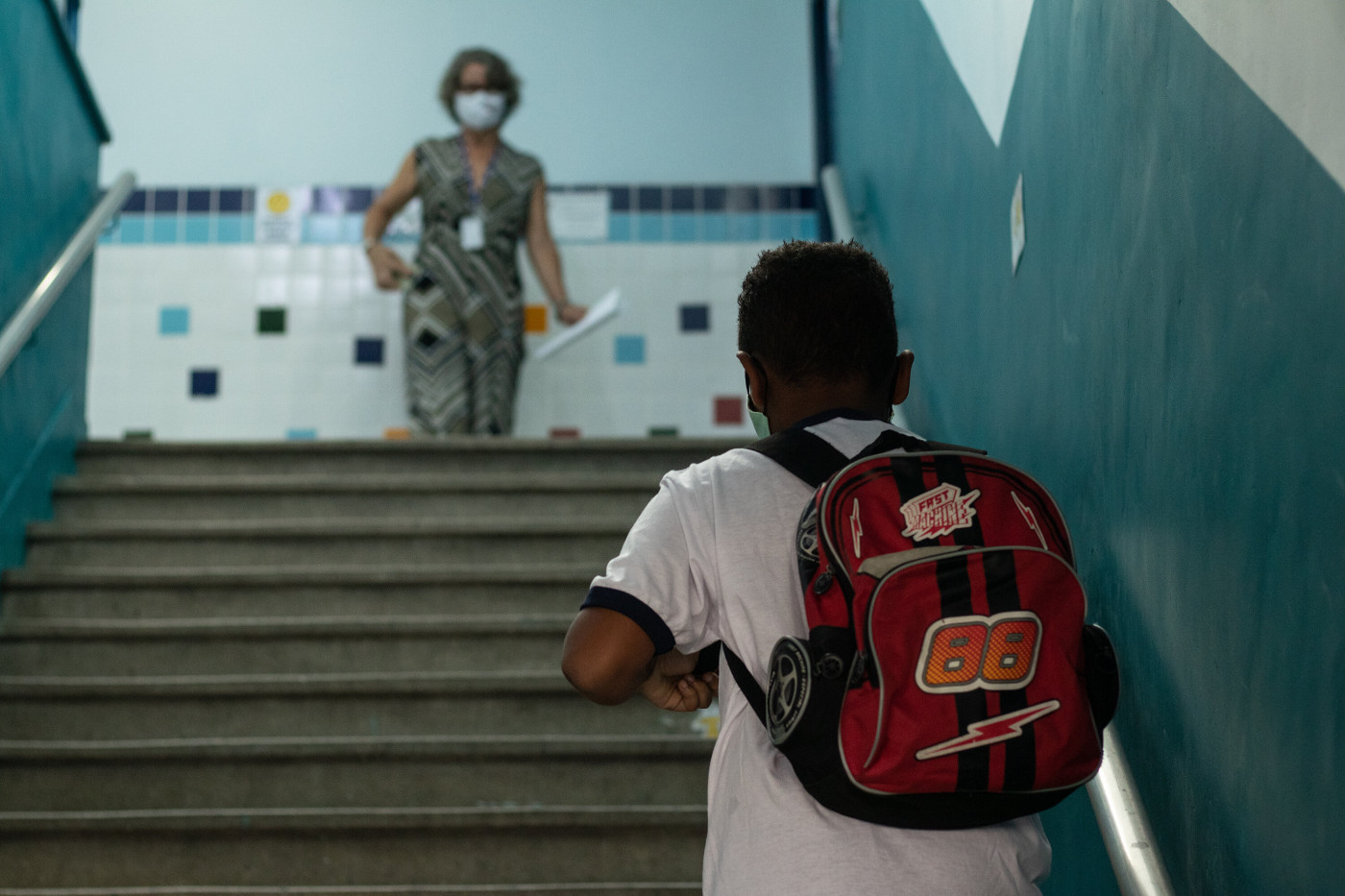 Profissional da educação aguarda chegada de aluno para volta às aulas presenciais