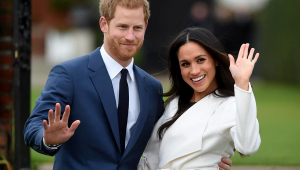 Abraços, o príncipe Harry e a atriz Meghan Markle posam acenando para as câmeras