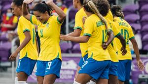 jogadoras de futebol do brasil se abraçando com uniforme do time (calção azul e camisa amarela)