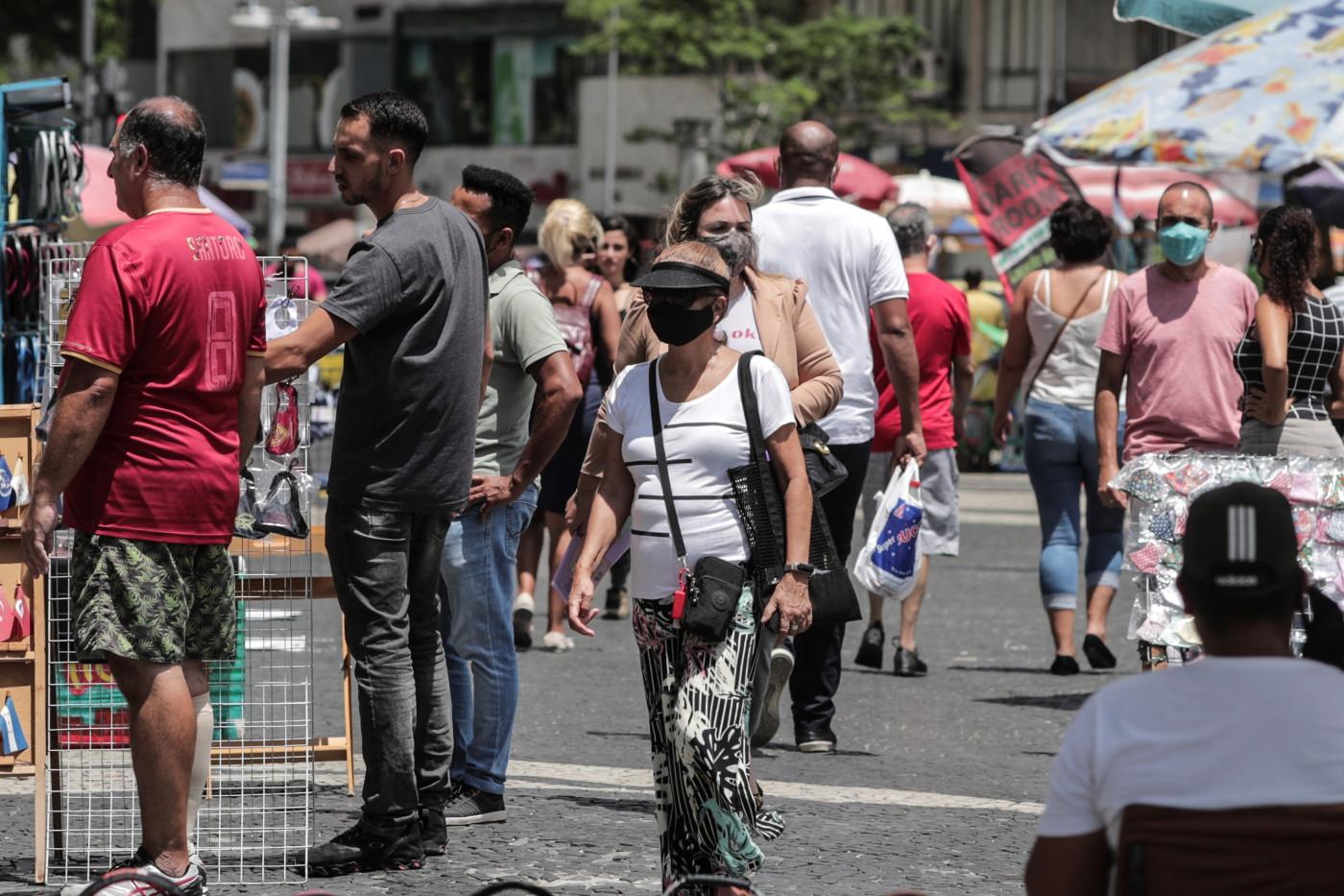 Pessoas caminham no centro do Rio de Janeiro utilizando máscaras de proteção contra a Covid-19