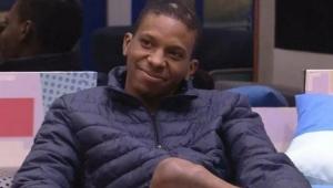 Lucas Penteado sentado em um sofá com um casco preto e sorrindo