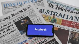 Celular com o logo do facebook colocado sobre uma pilha de jornais australianos