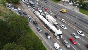 Vários caminhões e carros em uma grande rodovia. Imagem vista de cima.