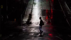 Homem anda em rua deserta de São Paulo durante período de lockdown