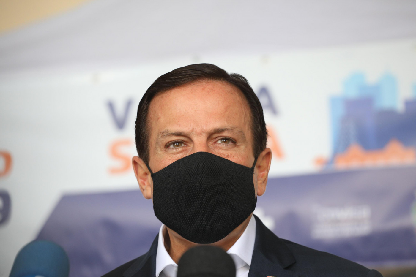 Homem de terno e gravata usando máscara preta diante de fundo com os dizeres 'vacina salva'