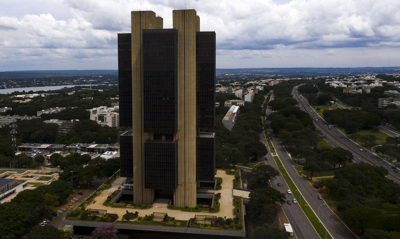 Imagem aérea do edifício sede do Banco Central, de prédio preto com colunas cor bege no meio de área descampada