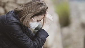 Mulher usa máscara branca, veste jaqueta preta e apoia a mão na cabeça