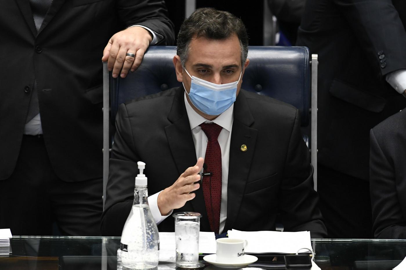 Rodrigo Pacheco, homem branco de terno preto, gravata vermelha e máscara