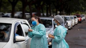 Profissionais da saúde vacinam pessoas em posto de imunização drive-thru