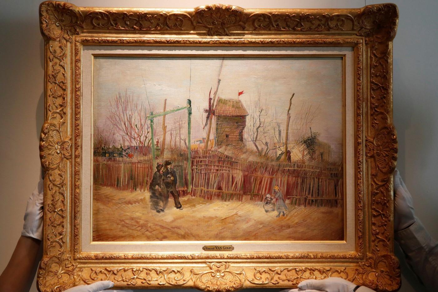 """Funcionários da Sotheby's Paris seguram a pintura de 1887 de uma cena de rua parisiense """"Cena de rua em Paris"""", do pintor holandês Vincent Van Gogh"""