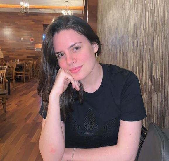mulher branca com mão apoiada no queixo olhando para a câmera