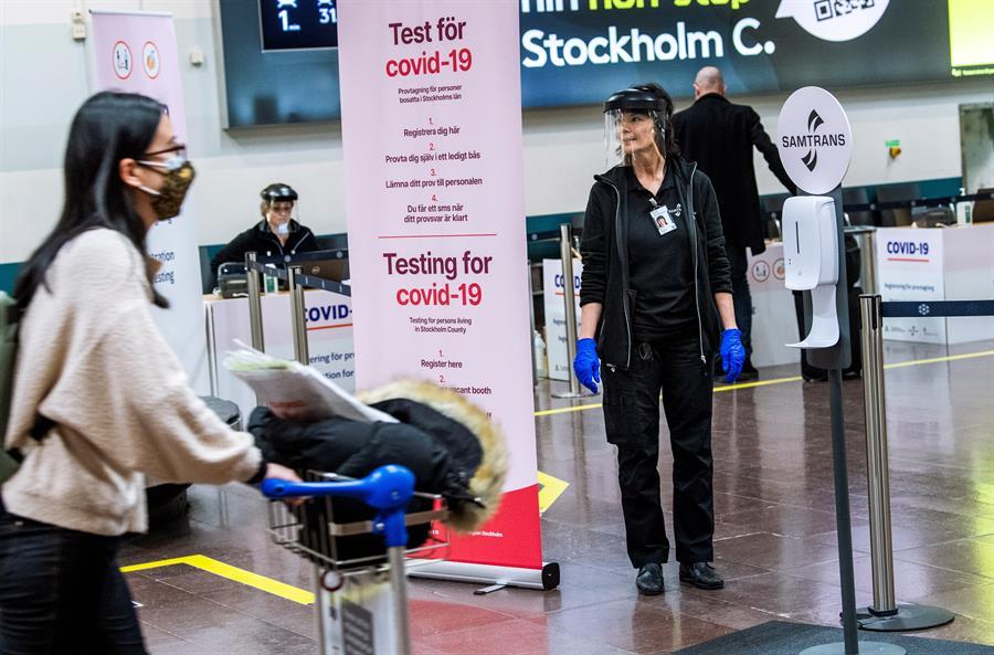 Funcionária do Aeroporto de Estocolmo, na Suécia, ao lado de placa que indica estação de testes de Covid-19