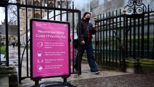 Usando máscara, mulher entra em área que está sendo utilizada para campanha de vacinação contra Covid-19 na Badia de Westminster, em Londres