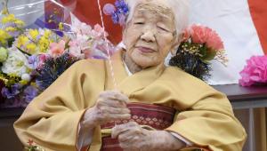 Mulher idosa de cabelos grisalhos trajando um kimono alaranjado
