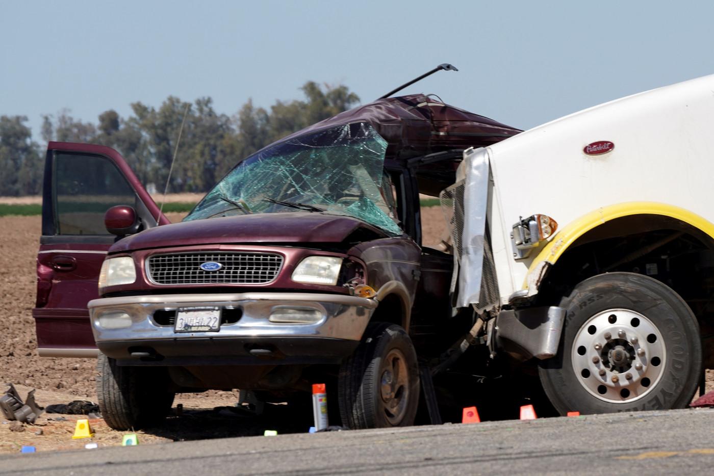 Carro roxo com parabrisa quebrado e amassado em todo o lado esquerdo pela cabine de um caminhão branco