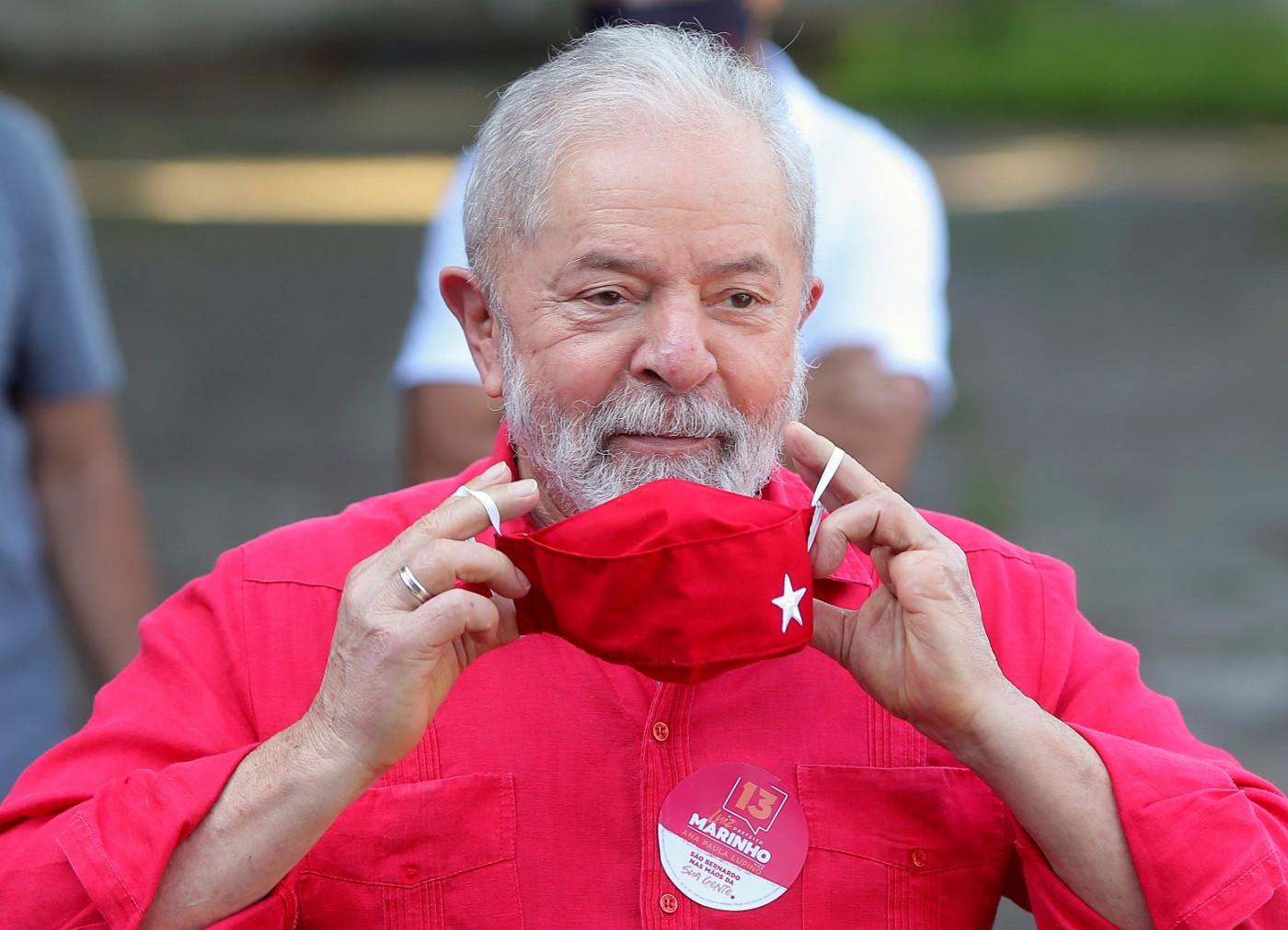Homem de cabelos brancos, camisa vermelha e máscara vermelha sorrindo