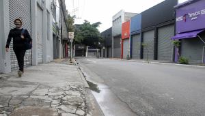 Homem andando de mochila e máscara em rua vazia com lojas fechadas