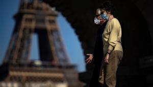 Pessoas usando máscaras passeiam em frente à Torre Eiffel em Paris, na França