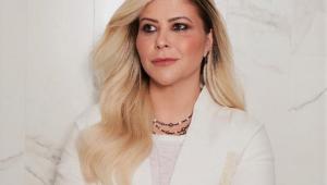 mulher branca e loira de braços cruzados olhando para o lado, com roupa branca e acessórios prata