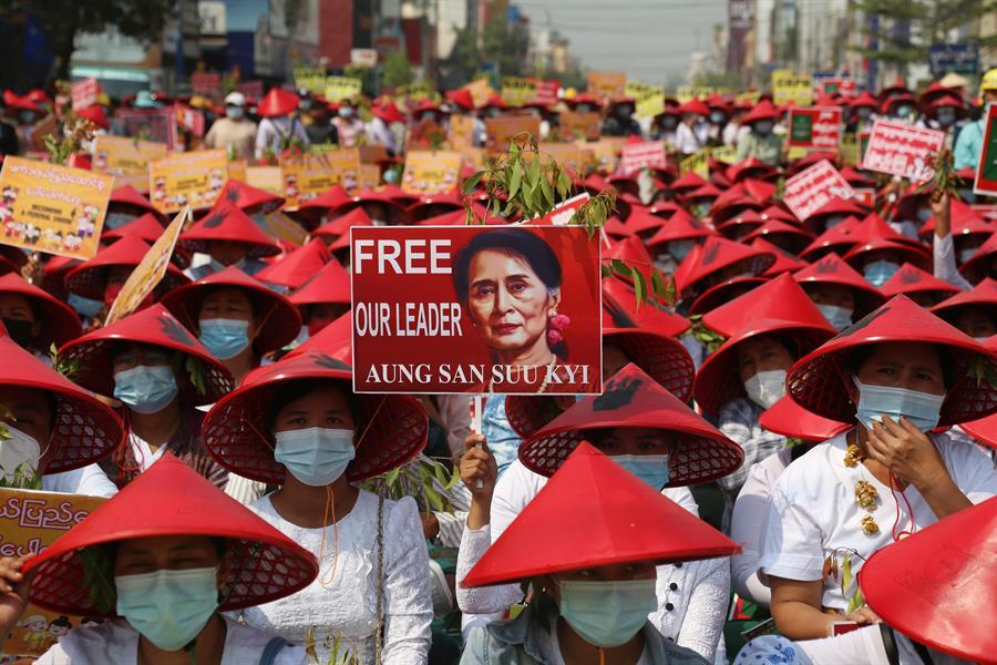 Em protesto contra o golpe militar no Myanmar, manifestantes vestem chapéus típicos do Sudeste Asiático pintados de vermelho e seguram cartazes pedindo a libertação dos presos políticos