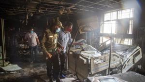 Hospital em Bangladesh destruído por incêndio com três homens olhando para uma cama