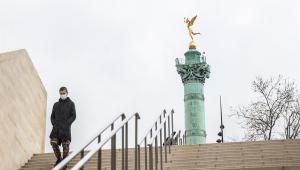 Homem usa máscara ao descer escadaria em Paris, na França