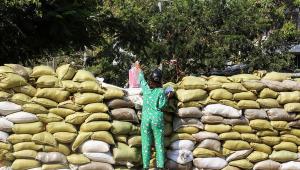 Mulher entrega uma sacola através de uma barreira improvisada que foi construída por manifestantes para impedir entrada das forças de segurança em Myanmar