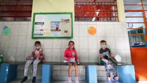 Crianças sentadas em um banco no pátio da escola, na cidade de São Paulo