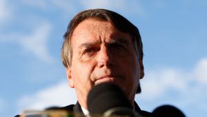O presidente Jair Bolsonaro dando entrevista com um microfone em sua frente