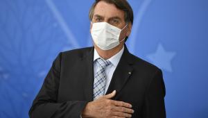 De terno, gravata e máscara de proteção, Bolsonaro leva a mão ao peito