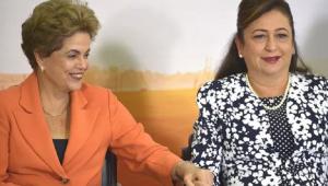 Duas mulheres de mãos dadas, uma usa um terninho laranja e outra um terninho florido