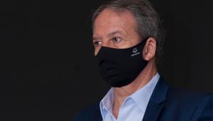 Em um fundo preto, o secretário de Saúde de São Paulo, Edson Aparecido de máscara