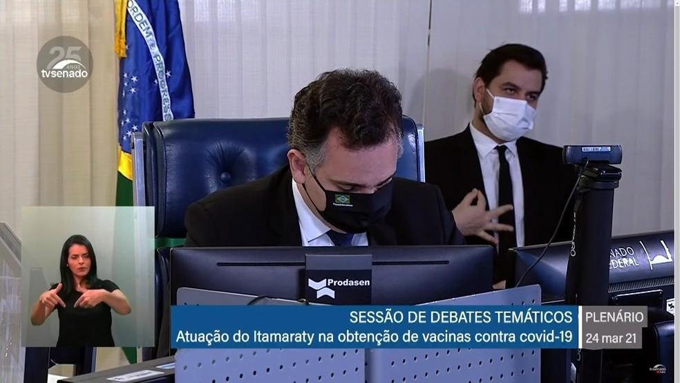 De máscara, pessoa faz gesto atrás de senador