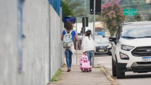 Duas alunas caminham em direção de uma escola na volta às aulas presenciais