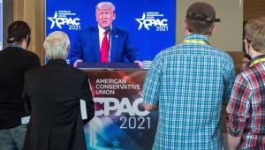 Apoiadores de Donald Trump assistem ao seu discurso na CPAC, na Flórida, através da televisão