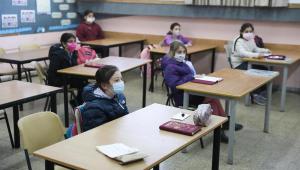 Crianças assistem aula com distanciamento social entre as carteiras e uso de máscara