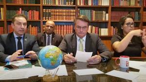 Três homens e uma mulher sentados em uma mesa. Presidente Jair Bolsonaro lê um papel. todos estão com o rosto virado para a câmera