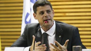 """Homem de terno e gravata pretos, com olhos claros e cabelos pretos gesticula enquanto fala em dois microfones. Ele está por trás de uma placa com o nome """"Bruno Funchal"""" e diante de um fundo marrom"""