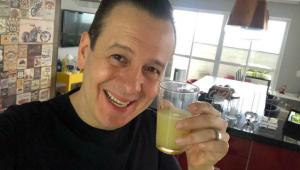 Selfie de Celso Zucatelli em sua casa com um copo de suco na mão