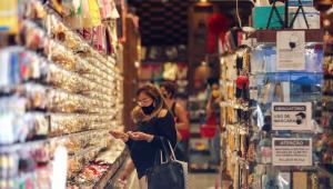 Usando máscara, clientes faz compras em uma loja respeitando os protocolos sanitários