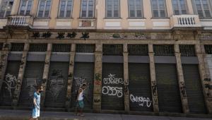 Pessoas caminham nas ruas com comércio fechado após aumento das restrições pela pandemia da Covid-19