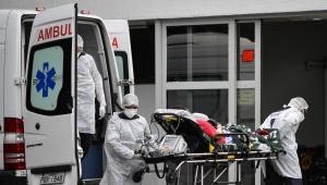Profissionais da saúde retiram paciente acamado de uma ambulância