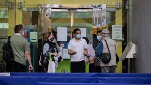 Grupo de pessoas em frente a um centro de vacinação fechado devido à suspensão temporária do uso da vacina contra Covid-19 da Pfizer-BioNTech em Hong Kong e Macau