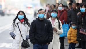 Chineses caminham nos arredores do mercado de Huanan, em Wuhan