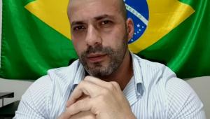 homem careca de blusa azulada com mãos cruzadas diante da bandeira do brasil