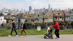 Família usando máscara de proteção caminha em frente às Painted Ladies em San Francisco, Estados Unidos